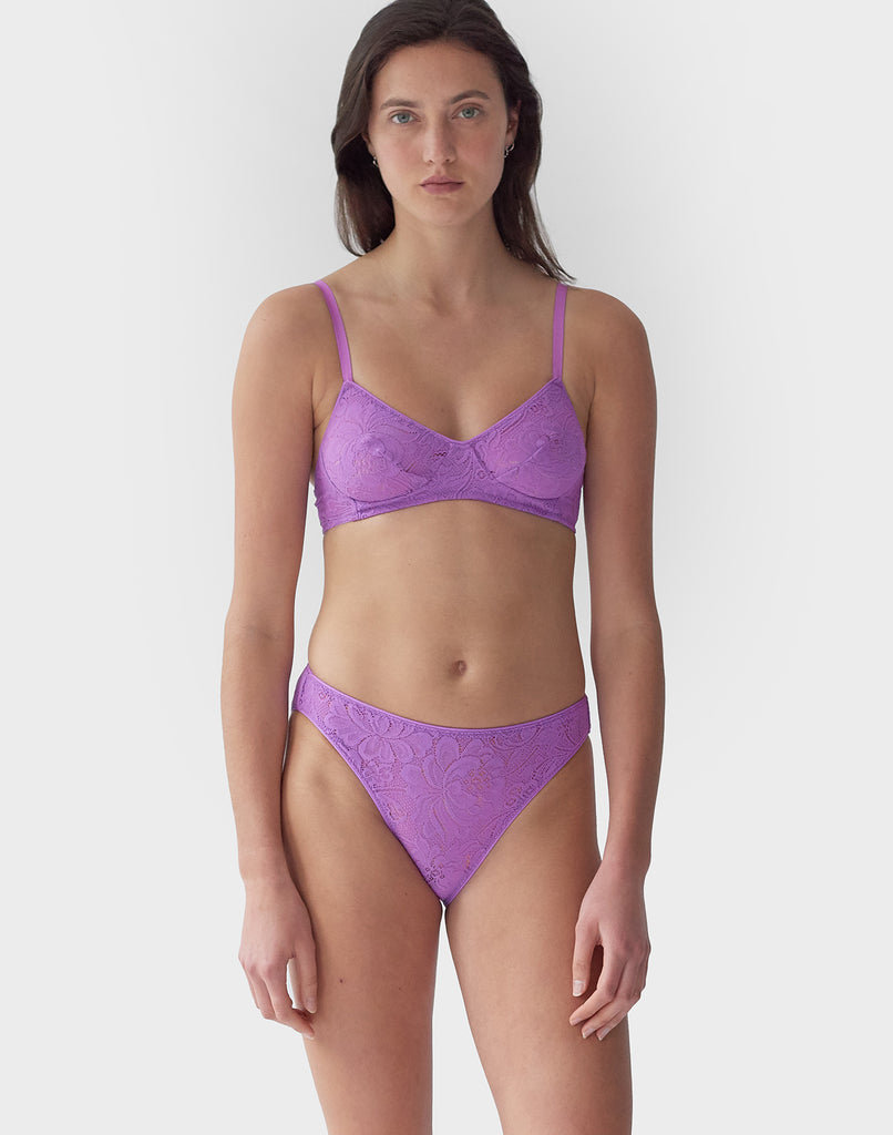 Woman wearing Purple, lace wireless bralette with matching straps, and matching Thong.