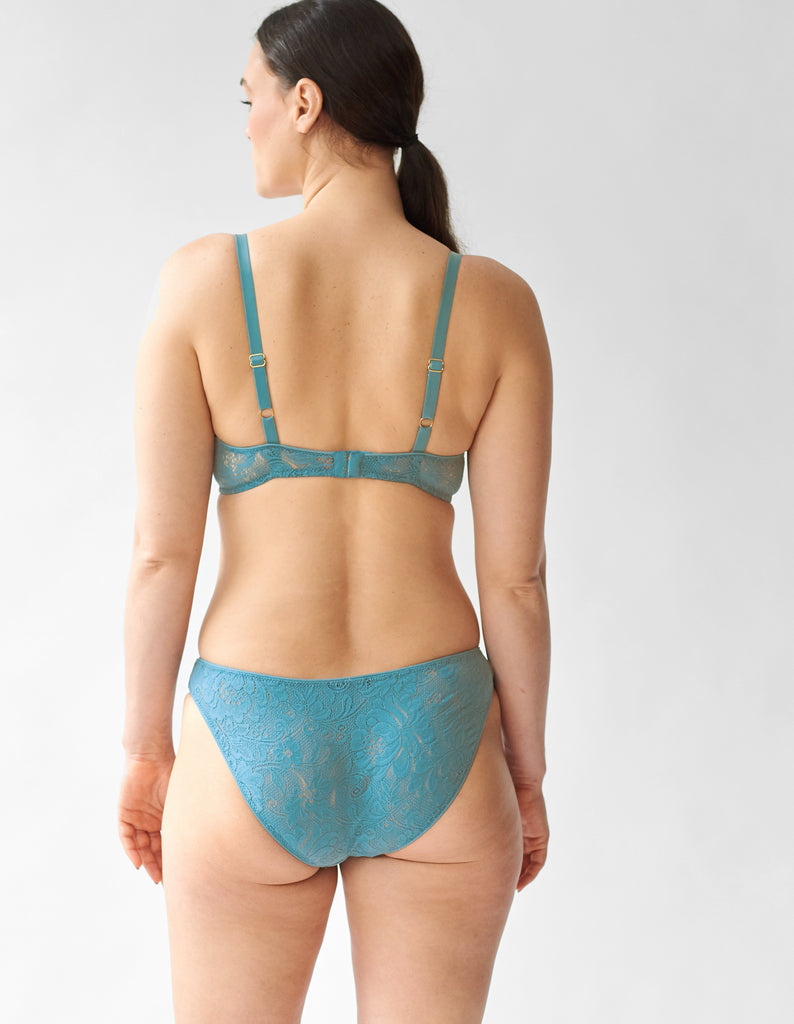 Backview of woman wearing blue wireless blue lace bra and matching panty