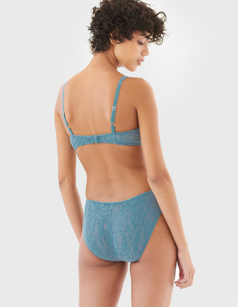 back of woman wearing blue wireless lace bra and matching panty