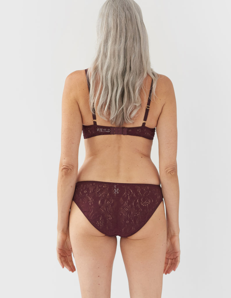 back of woman wearing dark red lace bra and matching panty