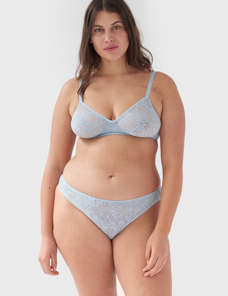 Woman wearing light blue, lace wireless bralette with matching straps, and matching panty