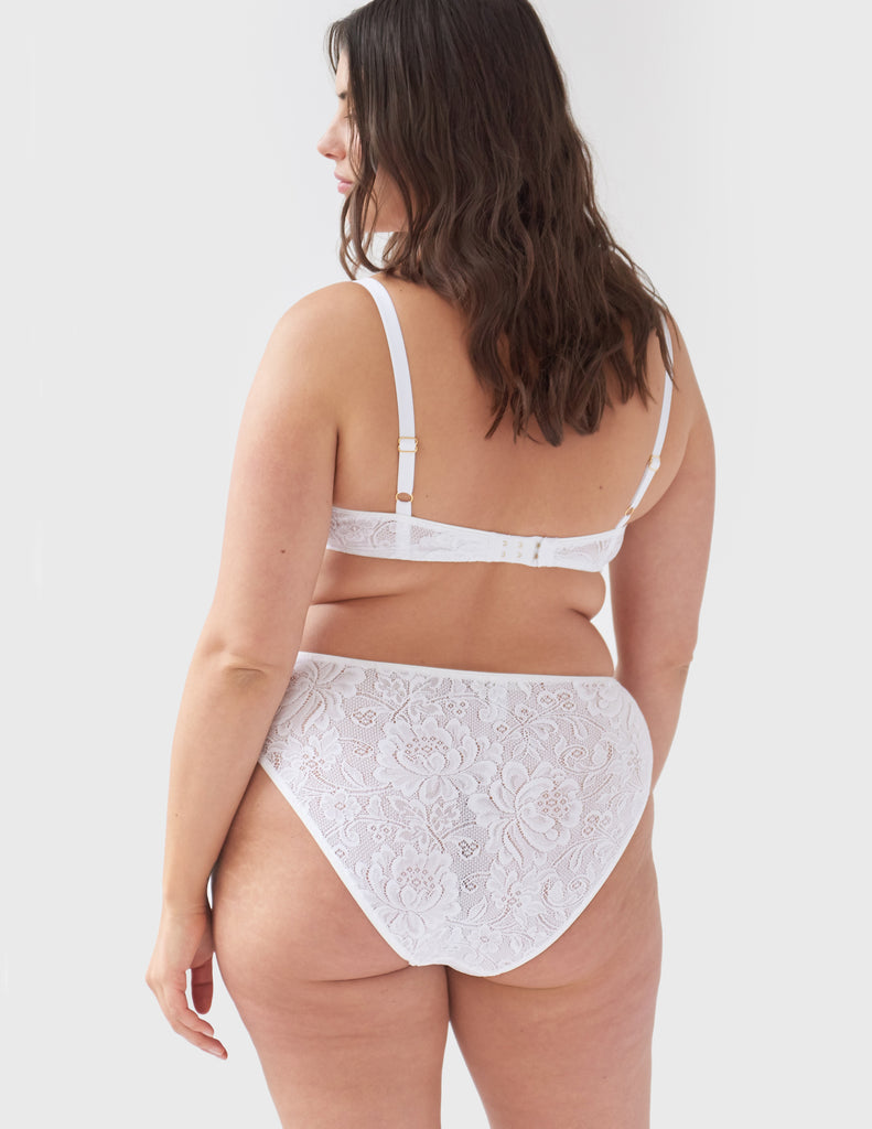 Face away, woman wearing white, lace wireless bralette with matching straps, and matching high-waisted panty.