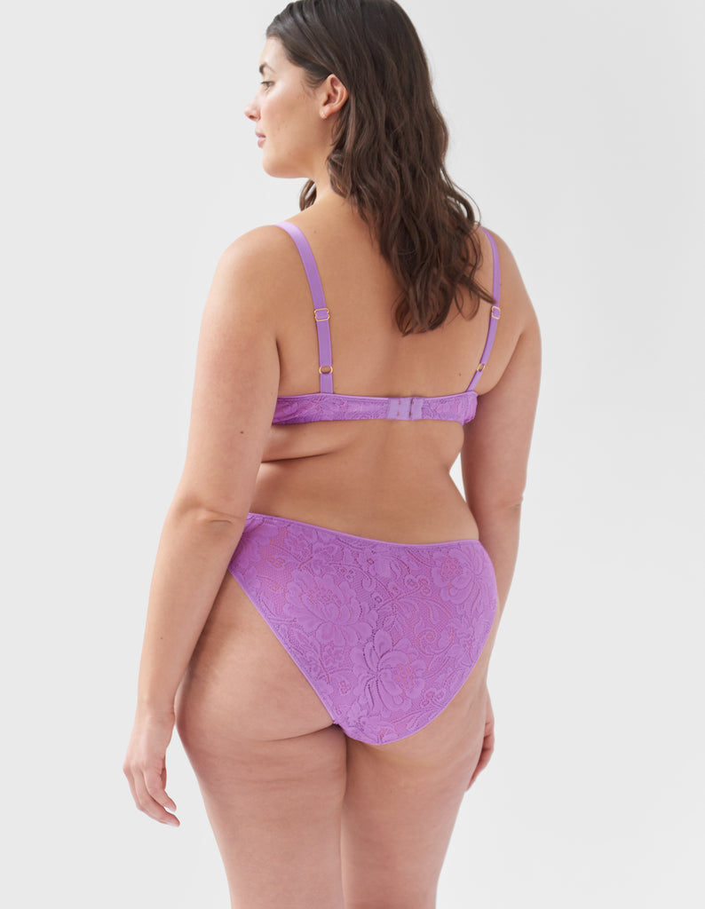 Woman wearing Purple, lace wireless bralette with matching straps, and matching high waisted panty.
