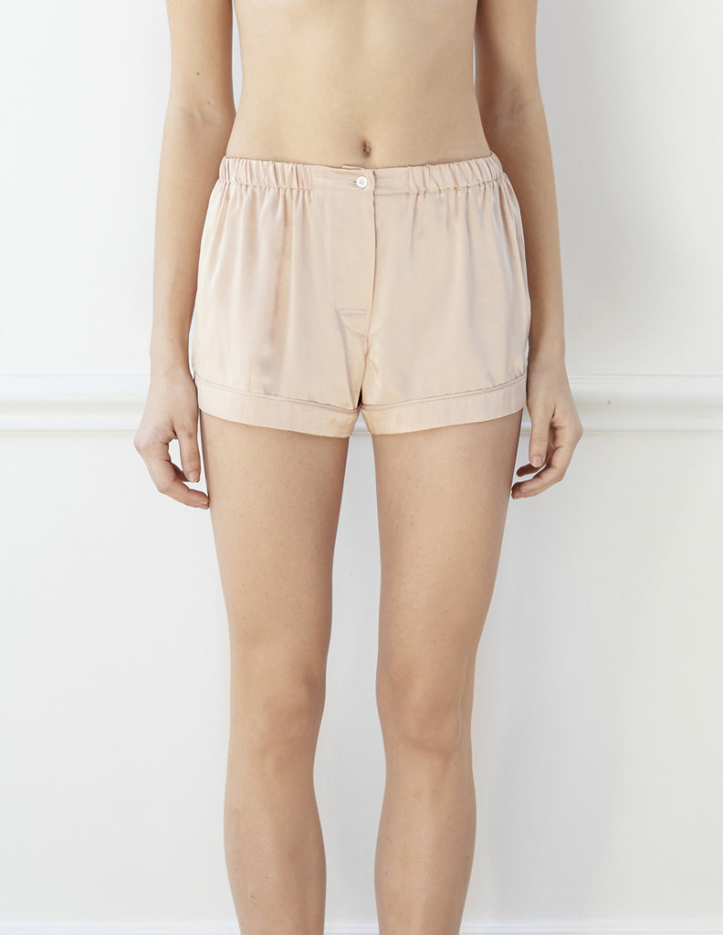 Woman wearing nude silk boxer shorts with contrast piping