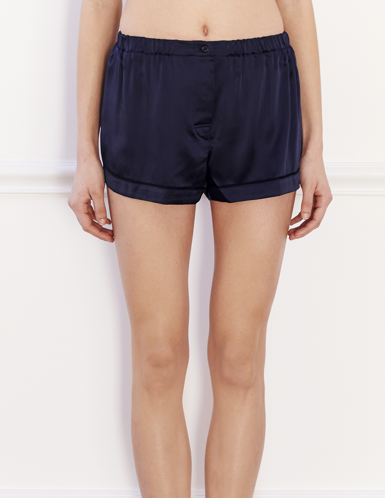 Woman wearing navy silk boxer shorts with contrast piping