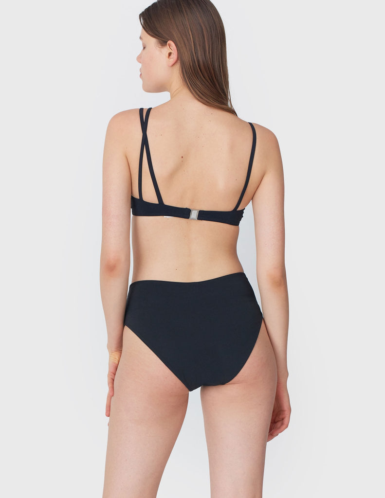 Back view of woman wearing an black bikini top with asymmetric crisscross straps with matching bottoms