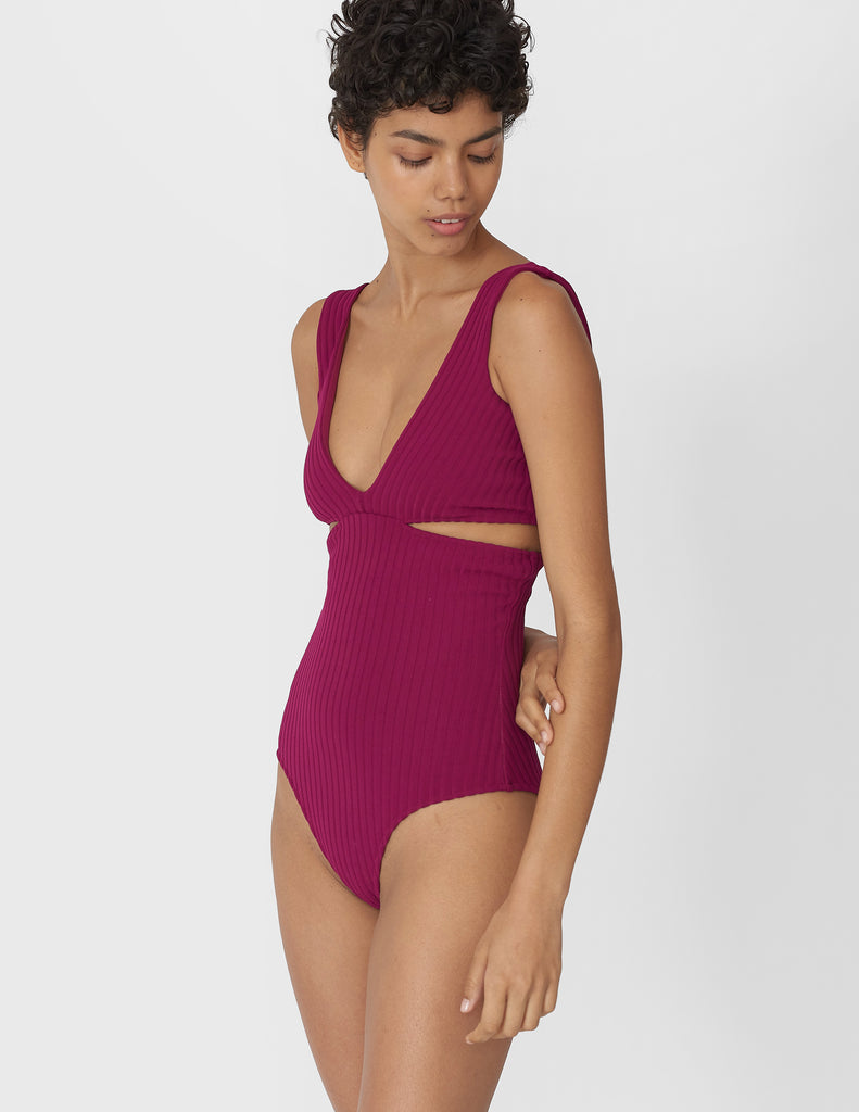 Woman wearing a berry ribbed one piece swimsuit with a deep v neckline and side slits