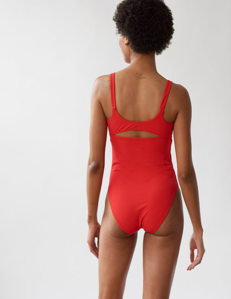 back of woman in red one piece with cutout