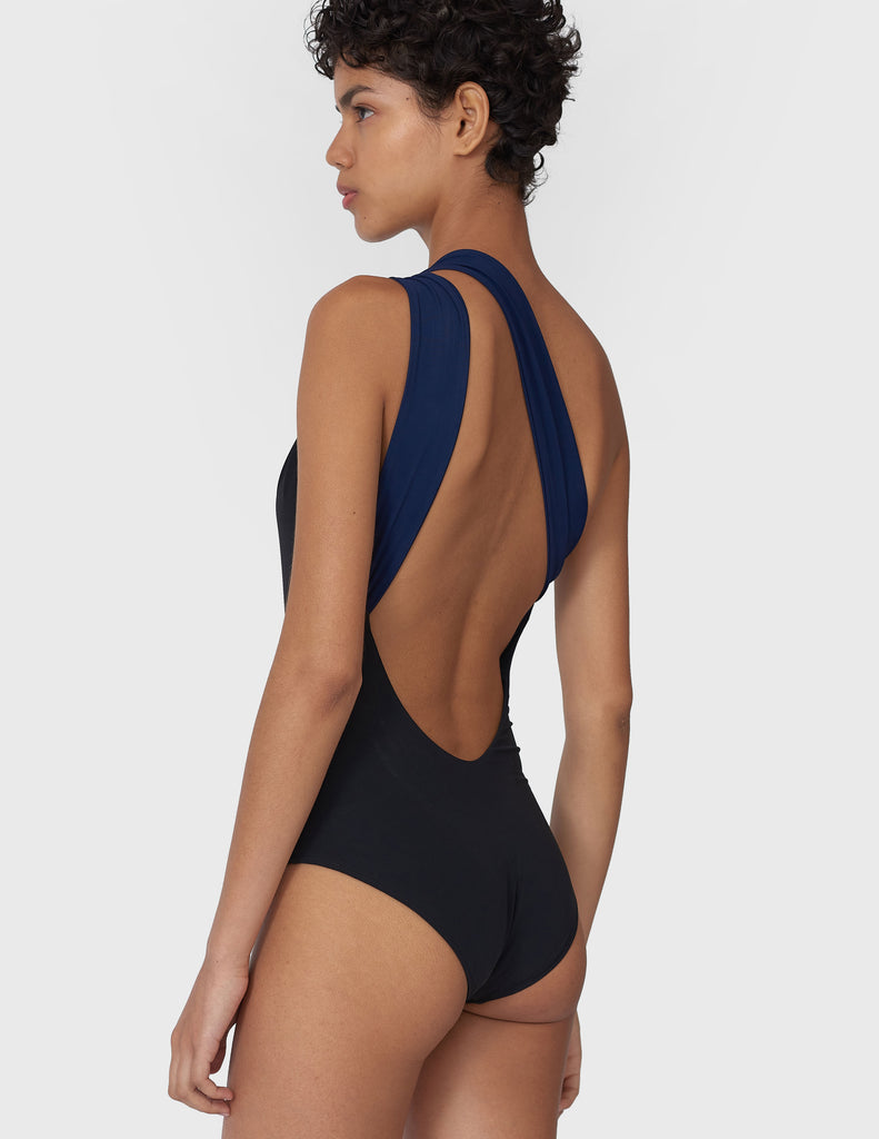 Back view of a woman wearing a black and navy one piece swimsuit