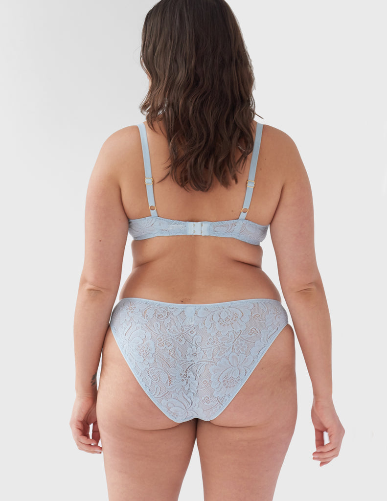 Face away, woman wearing light blue, lace wireless bralette with matching straps, and matching panty