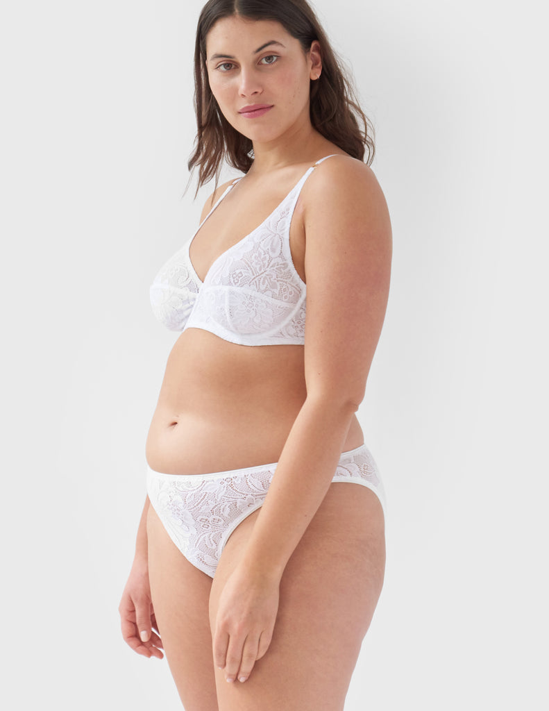 Woman wearing white, lace mid-rise panty with matching underwire bralette.