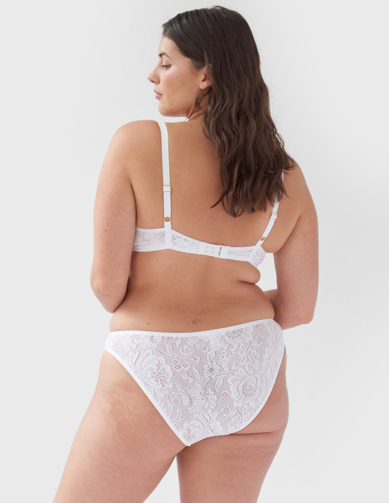 Face away, woman wearing white, lace mid-rise panty with matching underwire bralette.