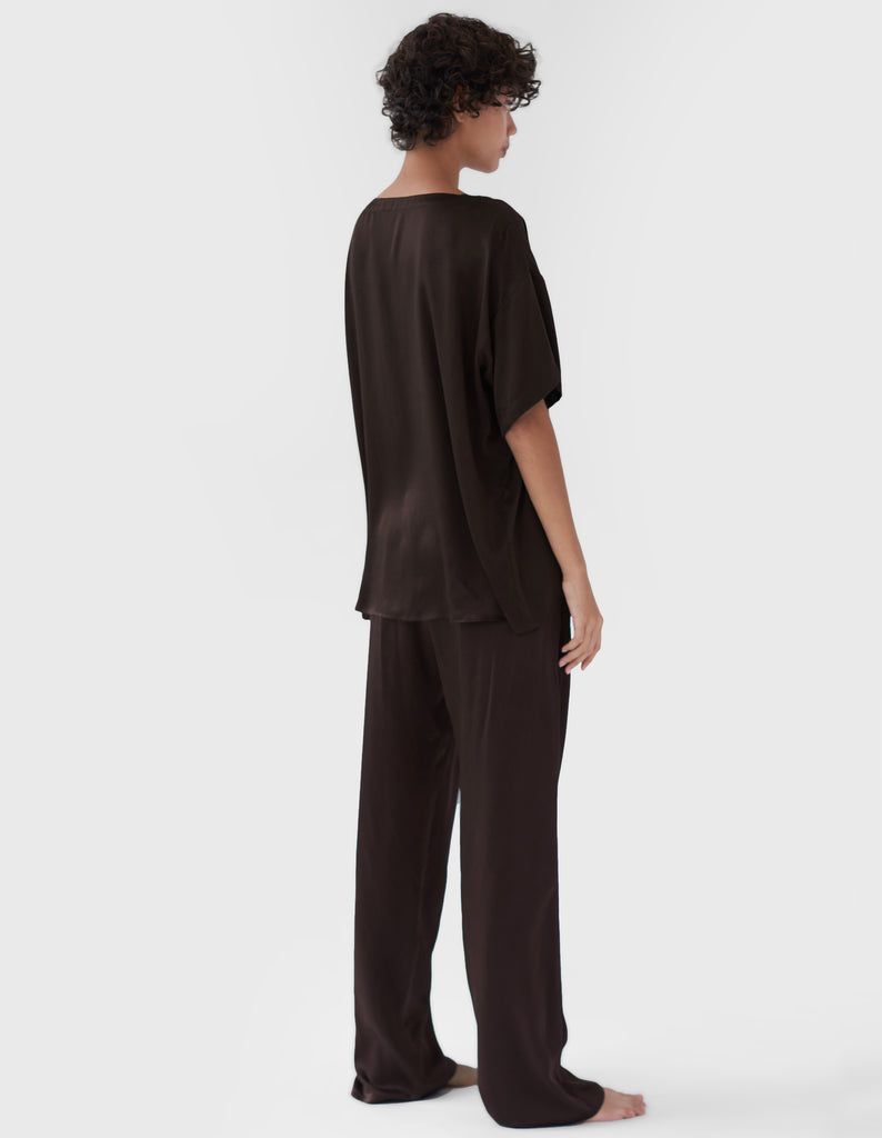 back of woman wearing brown silk t-shirt and matching pants