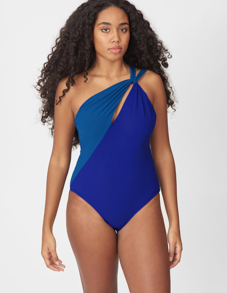 Front view of a woman wearing a blue and navy one piece swimsuit