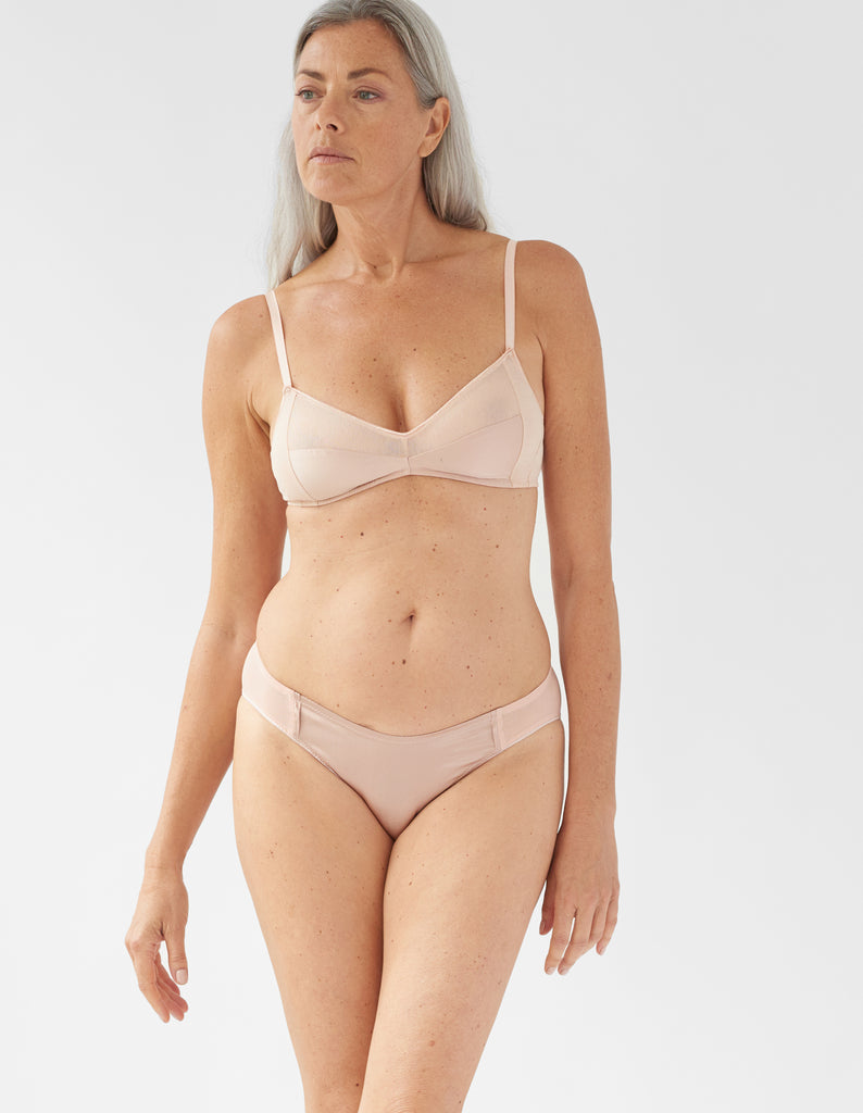 Front view of model wearing beige bralette and matching panty.