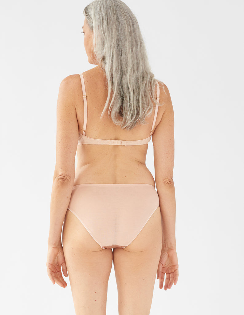 back of woman wearing beige  bra and matching panty