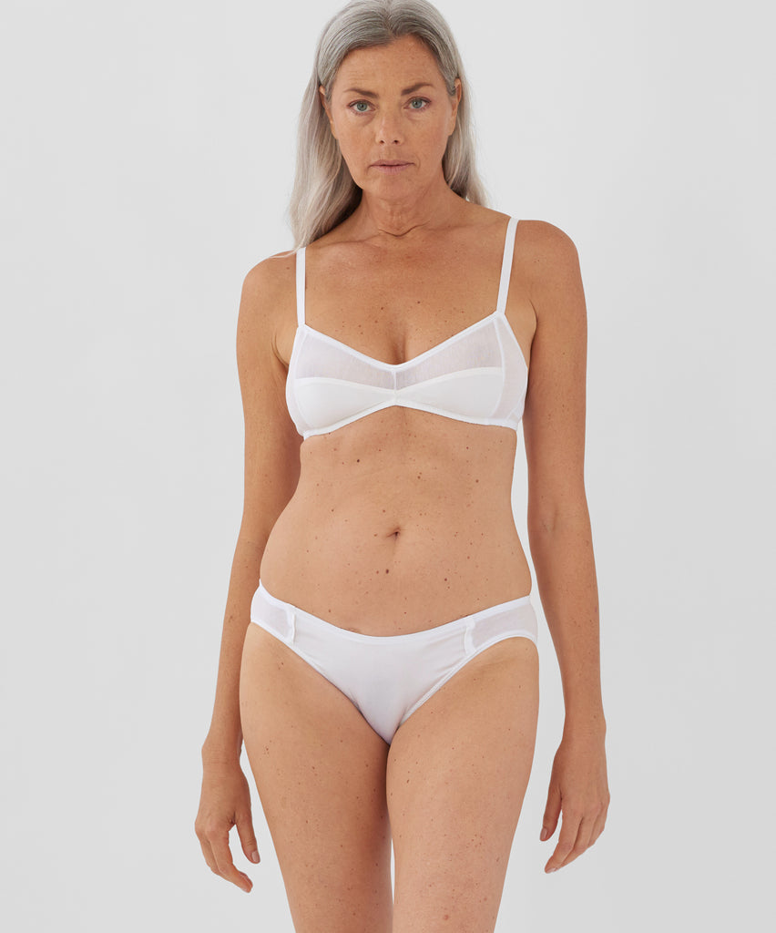 Front view of model wearing white bralette and matching panty.
