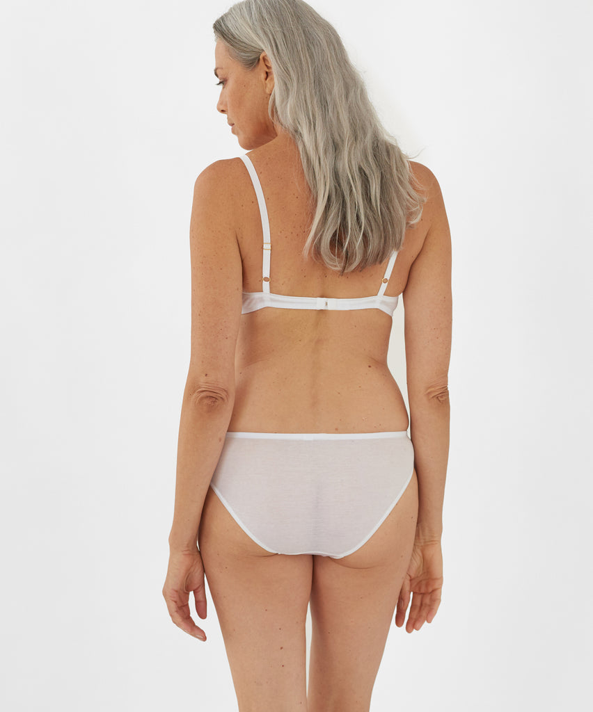 Back view of model wearing white bralette and matching panty.