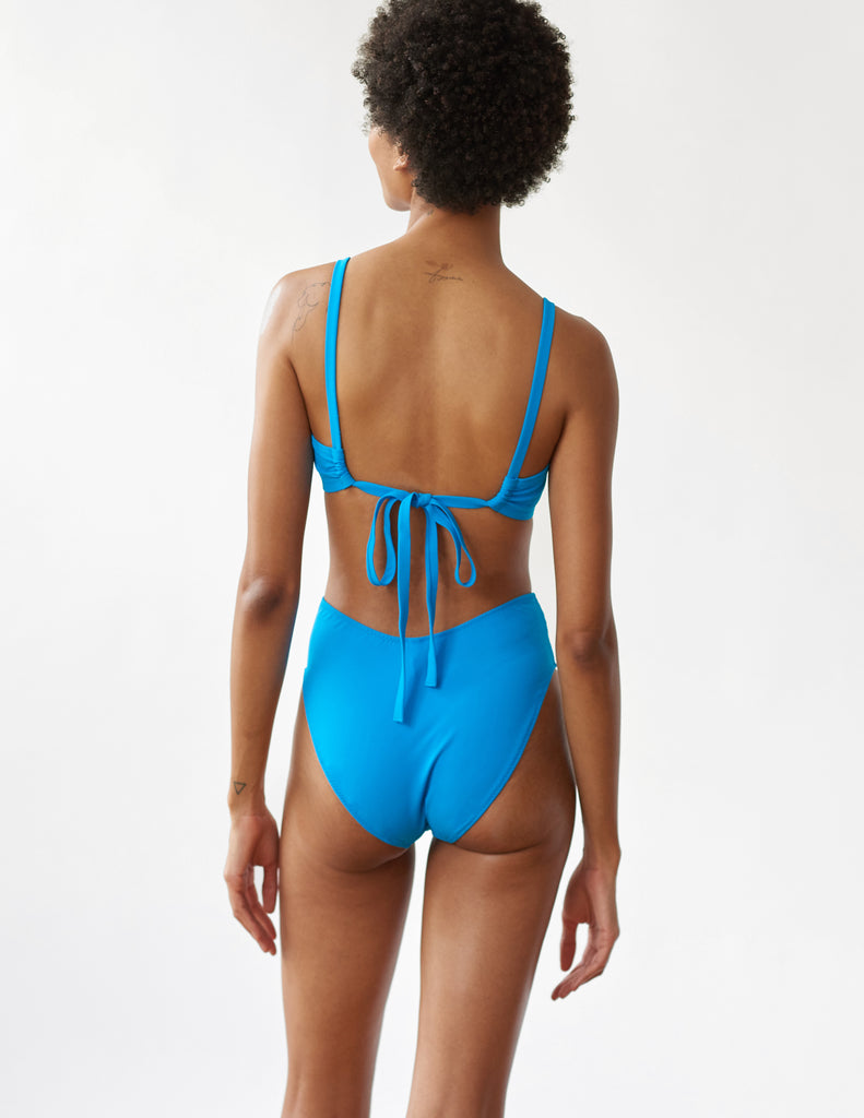back of Woman wearing blue two pice bikini with adjustable ties at back