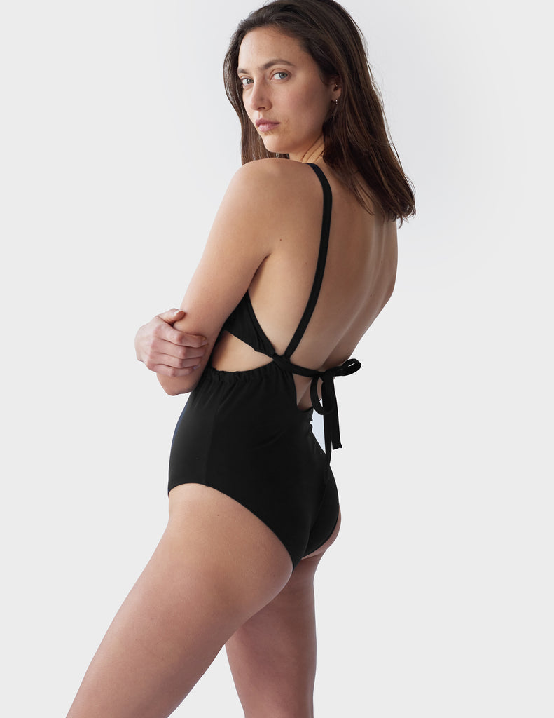 Side view of woman wearing a Black one piece swimsuit with side cut outs and a tie in back
