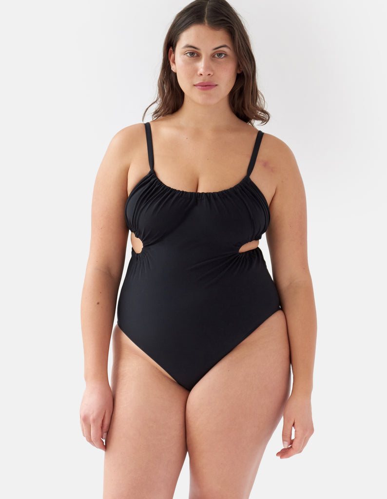 Front view of woman wearing a Black one piece swimsuit with side cut outs and a tie in back