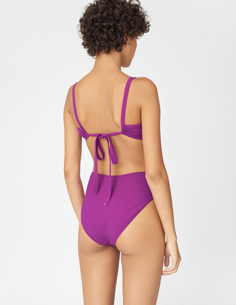 Back view of woman wearing a purple bikini bottom with matching purple bikini top