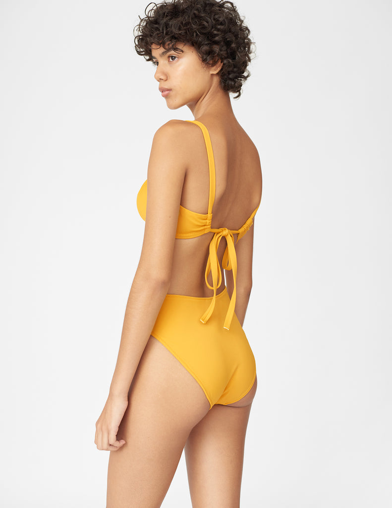 Back view of woman wearing a yellow bikini bottom with matching yellow bikini top
