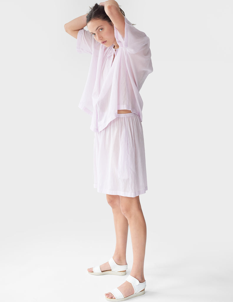 Woman's side and hands above, wearing a pale lavender cotton-chiffon boxy open-neck t-shirt with matching shorts
