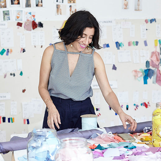 A woman working at a table with colorful fabric swatches