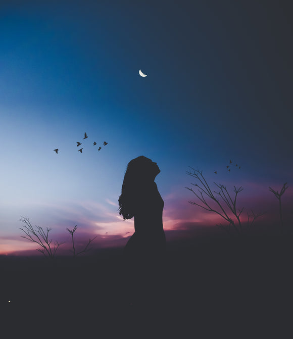 Woman looks towards  a half present moon. Her back drop the blue orange violet sky at sunset.