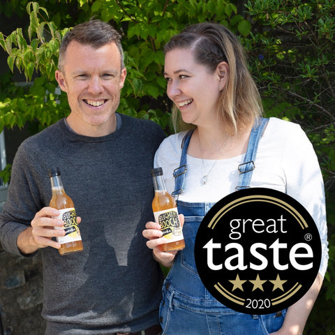 Alana and Mark, founders of Blighty Booch Kombucha holding a couple of bottles.