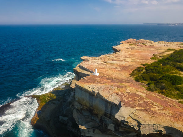 Stock image of waterfront cliff and white obelisk marker at Shark Point in Sydney