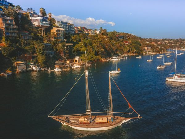 Wooden sailboat and luxury waterfront properties in the distance - Sydney, Australia