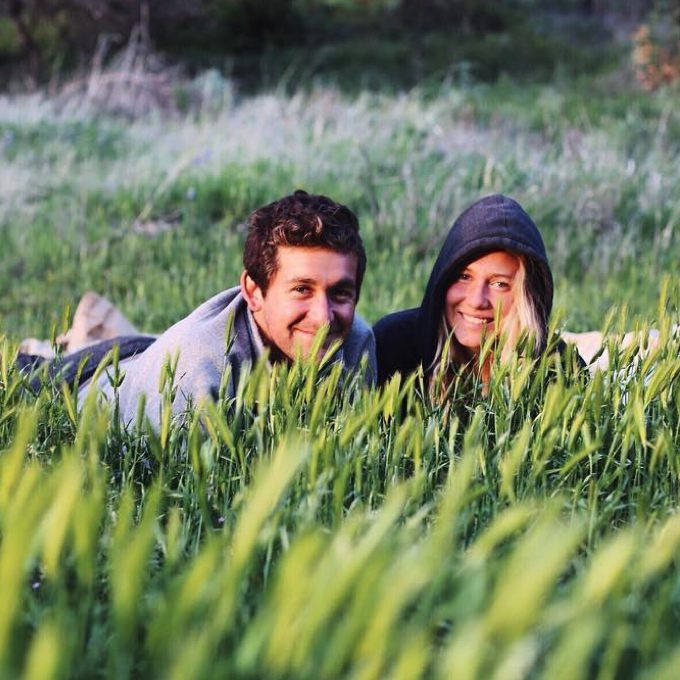 Tiny Life Supply ambassadors Matt & Sarah lying in a grassy field.