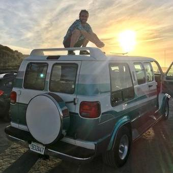 Tiny Life Supply ambassador Scott Hanson posing for a photo crouching on top of his green retro dodge vanlife conversion van.