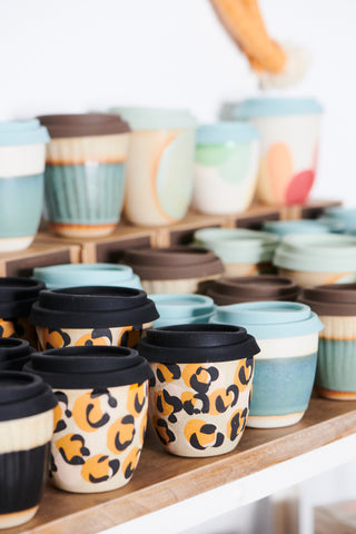 Kim Wallace Ceramic Leopard Print Coffee Cups on a shelf with lid