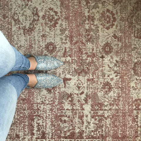 Grey patterned Moroccan babouche leather slippers worn at home with jeans on a pink rug
