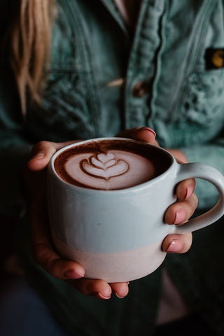 A female holding a large decadent Grounded Pleasures hot chocolate in a ceramic mug
