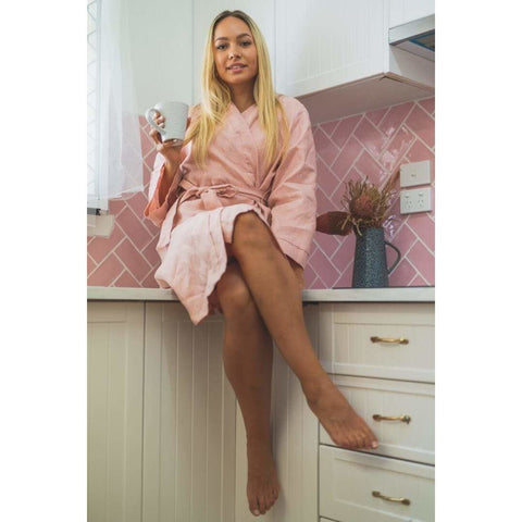A blonde sitting on the kitchen bench wearing the Jade and May Dusky Rose Pure Linen Kimono Bathrobe drinking a coffee looking at the camera