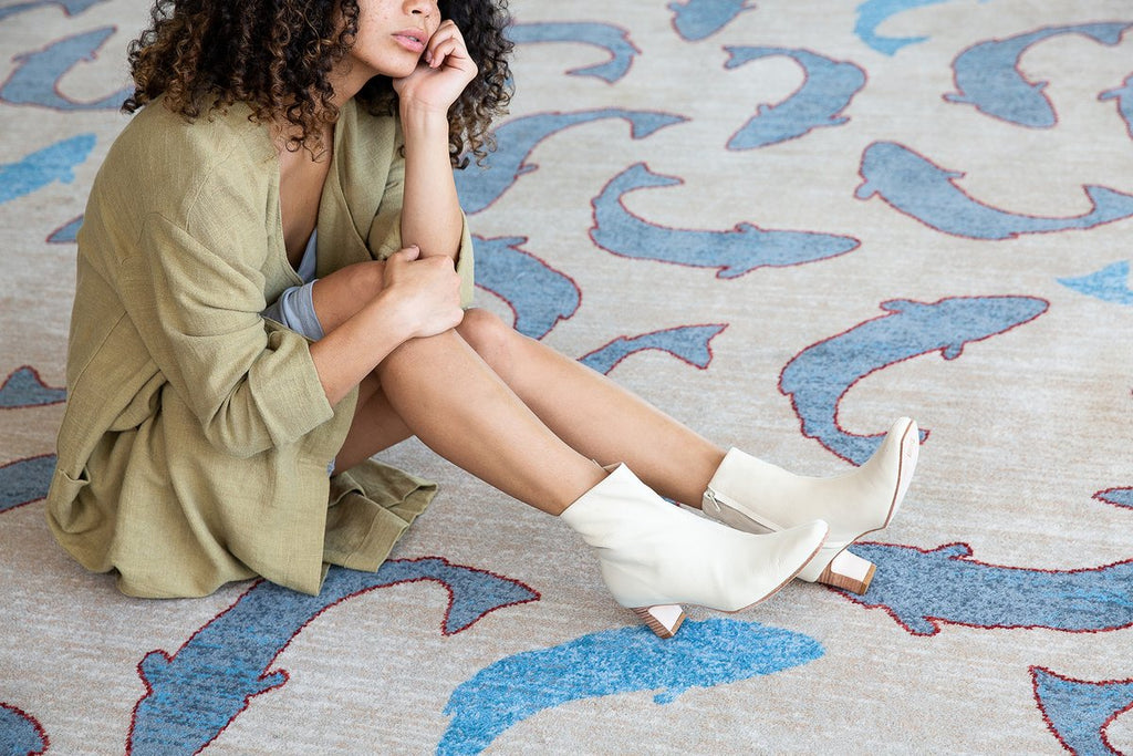 woman sitting on carpet wearing bolena bone booties