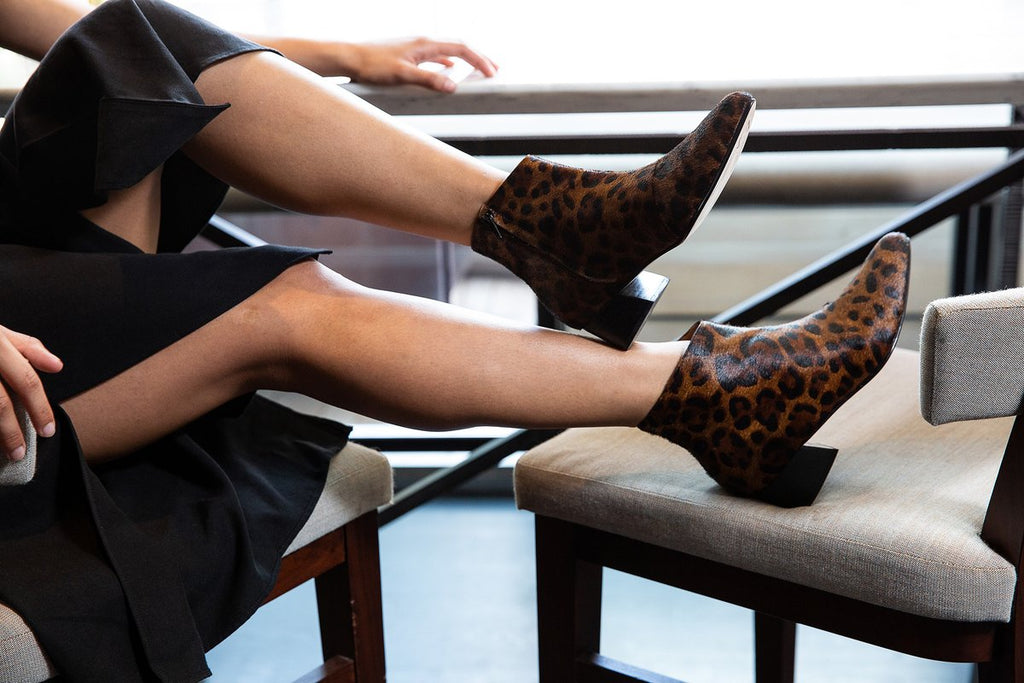woman sitting in chair wearing leopard print booties