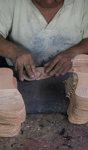 fortress of inca factory tour - person working on leather insoles for shoes