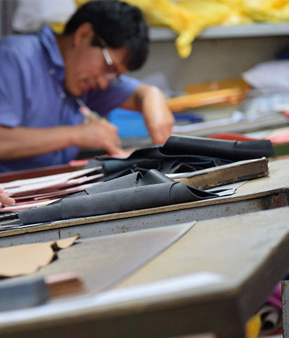 fortress of inca factory tour - worker meticulously carves the outer edge on the leather sole on a pair of adriana coco boots.