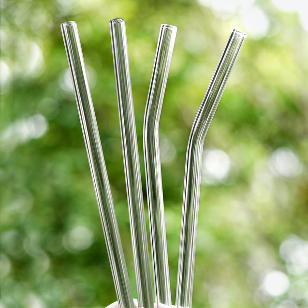 holding 2 straight and 2 bendy glass straws outdoors