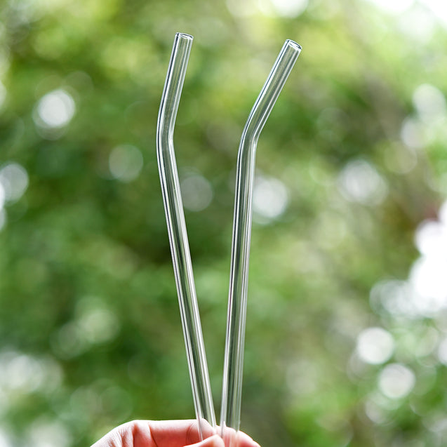 hands holding 2 straight glass straws during the day outdoors 8mm wide
