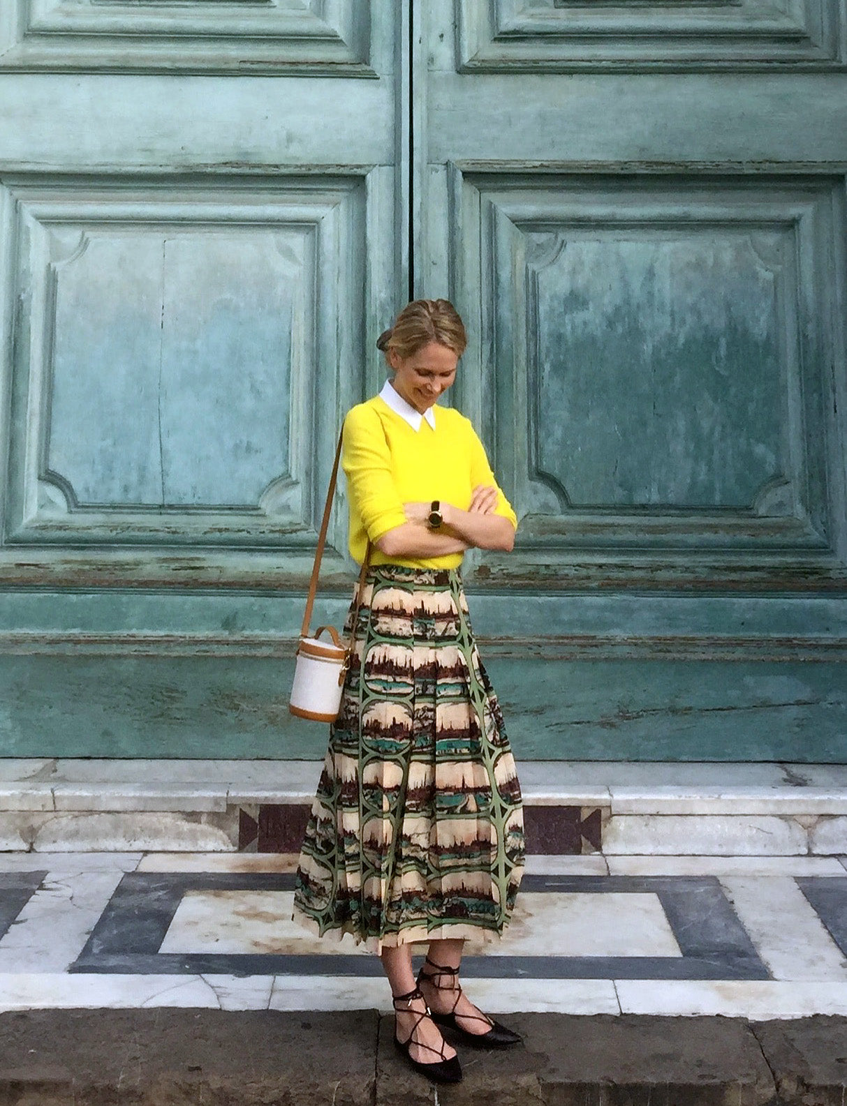 Indre Rockefeller arms crossed yellow sweater with printed skirt