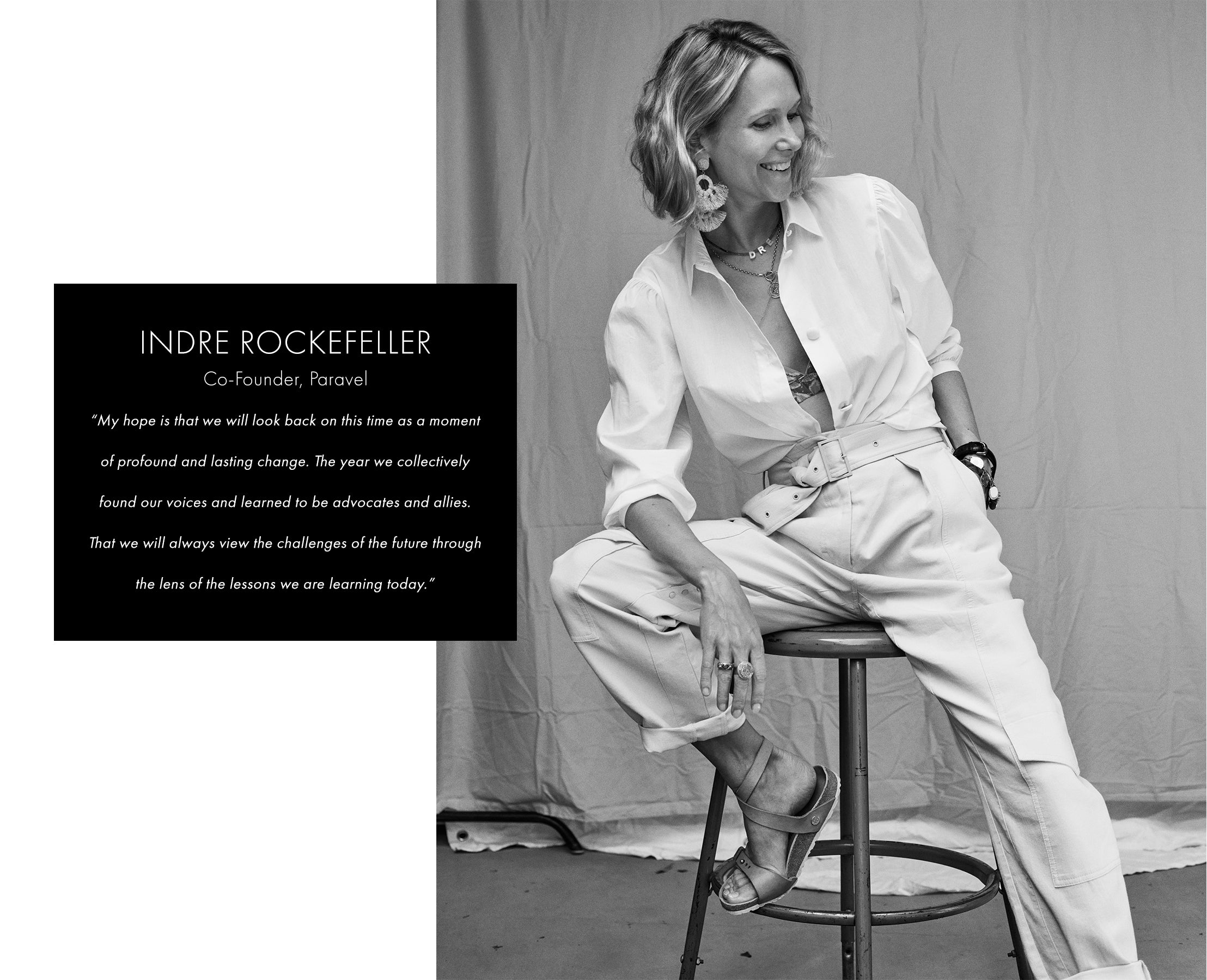 Indre Rockefeller sitting in white button down and trousers on stool