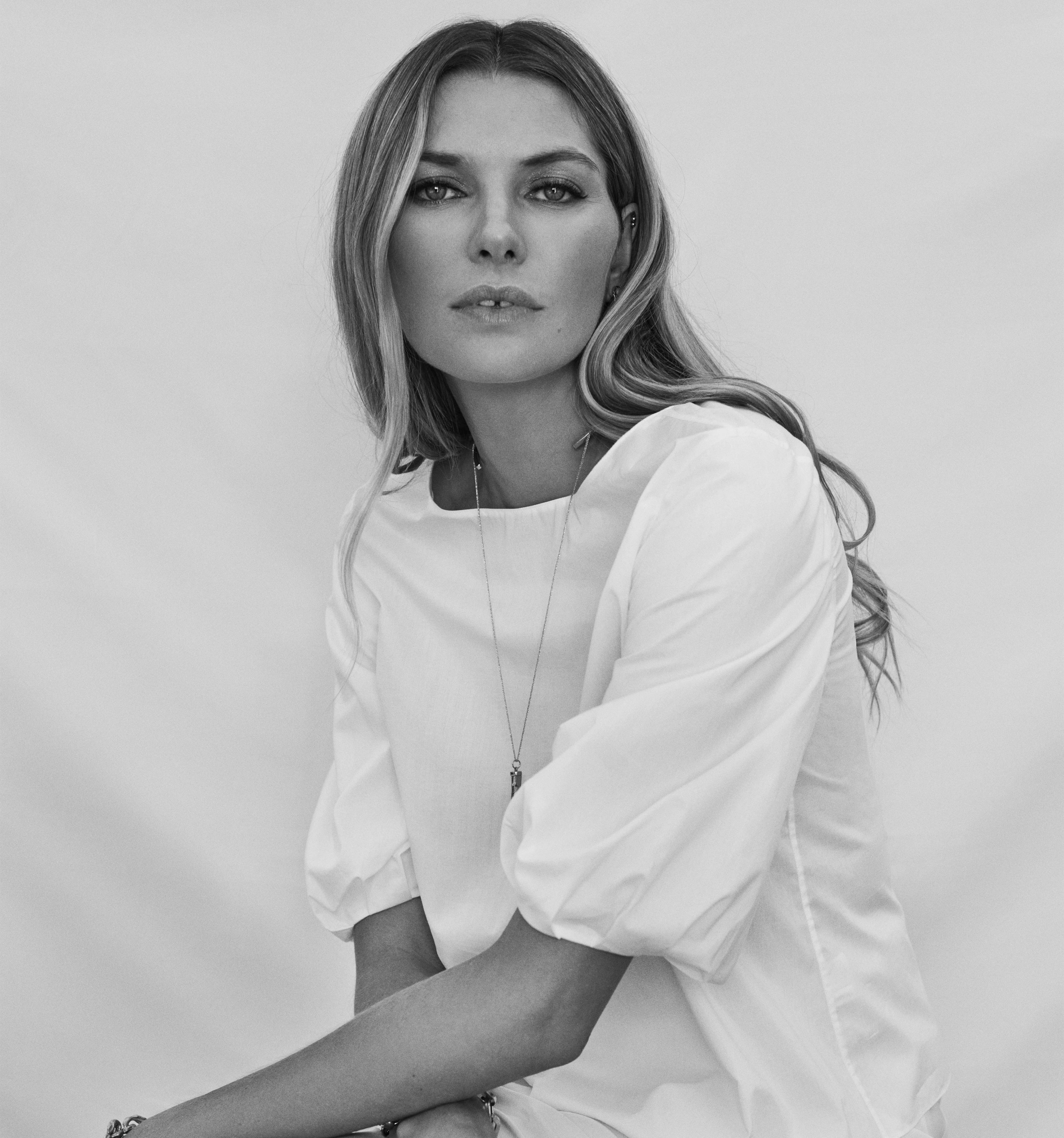 Jessica Hart sitting in white puff sleeve blouse