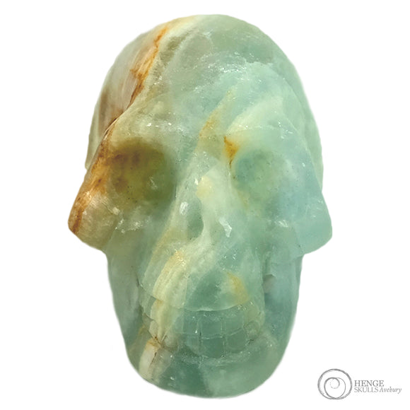 Small light blue crystal human skull head with orange and white stripe running through the skull