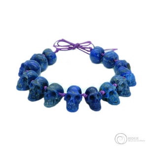 Deep blue bracelet with 14 mini human crystal skulls on purple bracelet
